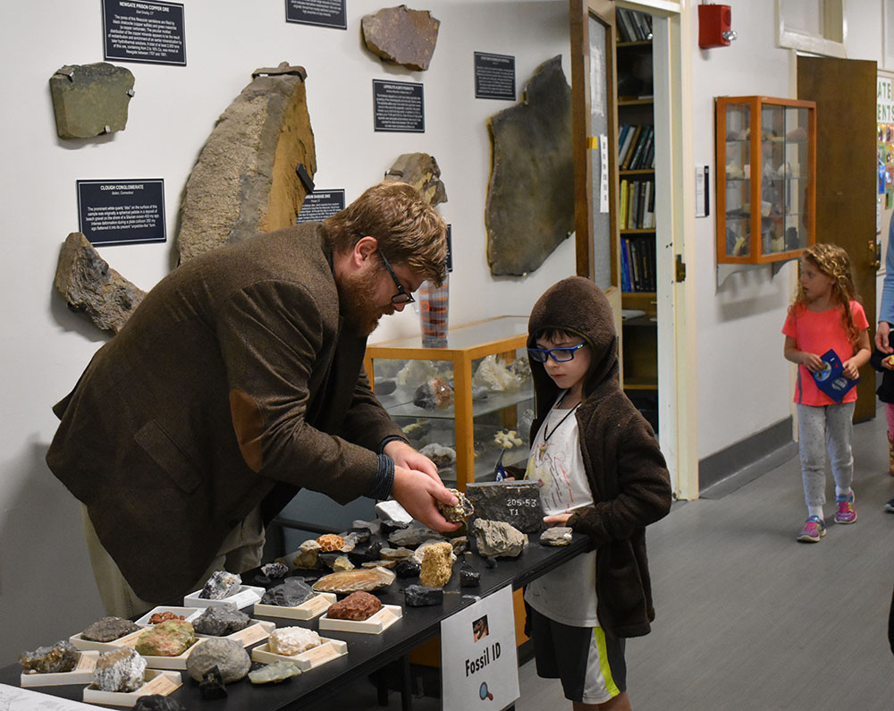 Student teaches kid about fossils at Earth Day Event